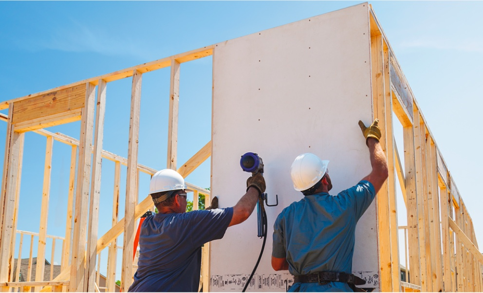 Workers attaching panels to a framed building, under a clear blue sky.