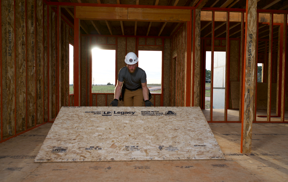 Worker placing a sheet of sub-flooring down in a new building under construction.