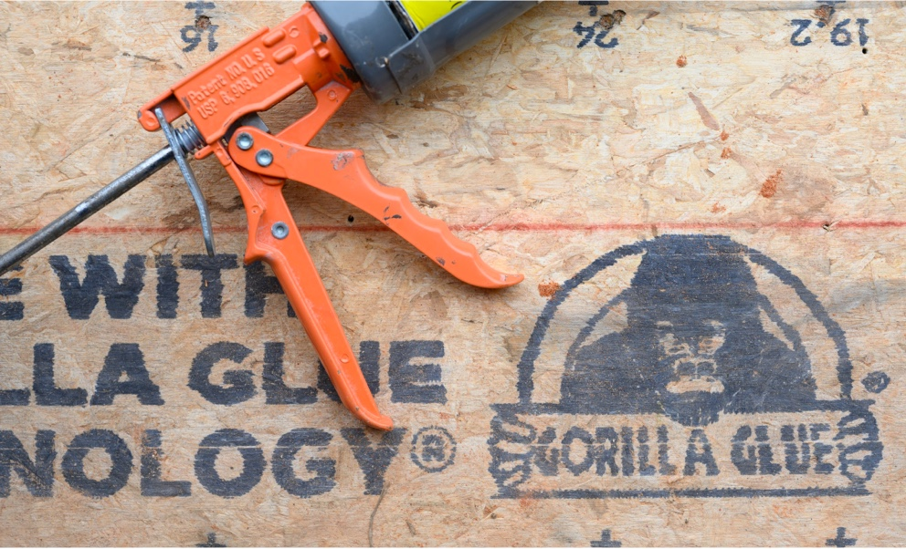 Close up shot of the Gorilla Glue logo on a Legacy panel, with a caulking gun resting on it.