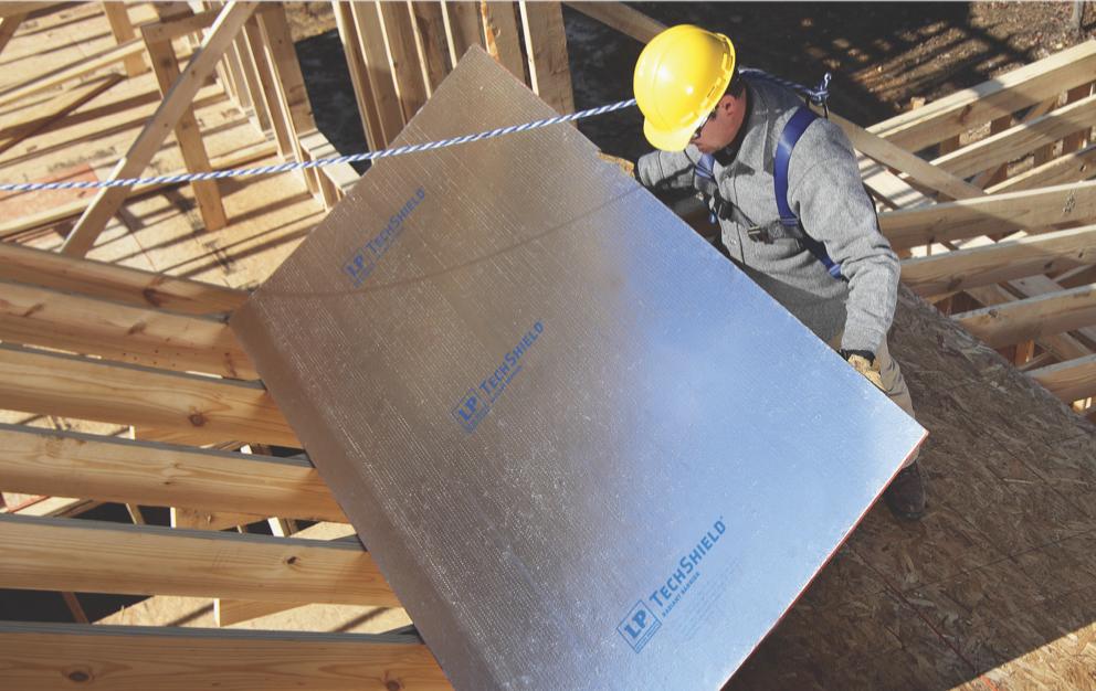 Ouvrier plaçant une feuille du produit anti-rayonnement TechShield sur un site en construction.