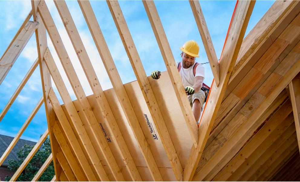 Un ouvrier sur une charpente de toit à forte pente, fixant une feuille de Techshield.
